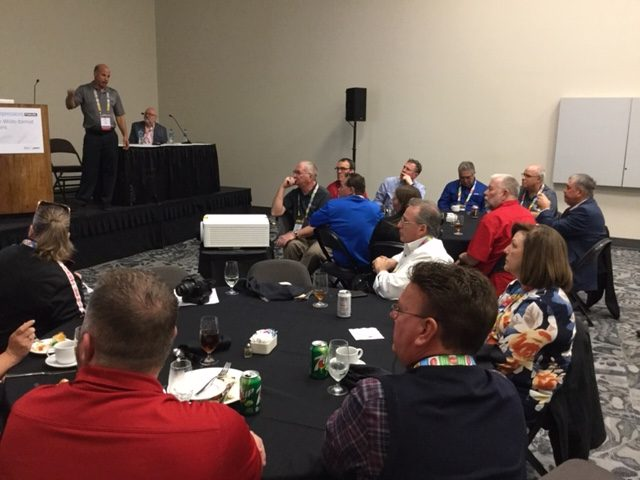 MikeGeorge (standing) and Roy Nance addressed a packed room of in-plant managers.